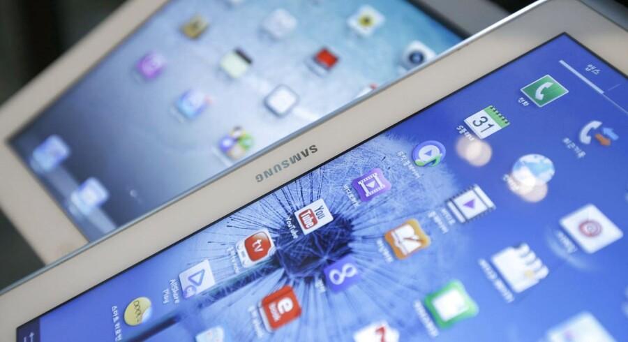Samsung kan fortsat sælge sine Galaxy-telefoner og -tavlecomputere i USA, efter at en dommer har afvist Apples krav om et salgsforbud. Forrest ses her en Galaxy Tab fra Samsung, bagest en iPad fra Apple. Det er lighederne i design og funktioner, der har været i søgelyset i den mange år gamle retssag. Arkivfoto: Kim Hong-Ji, Reuters/Scanpix