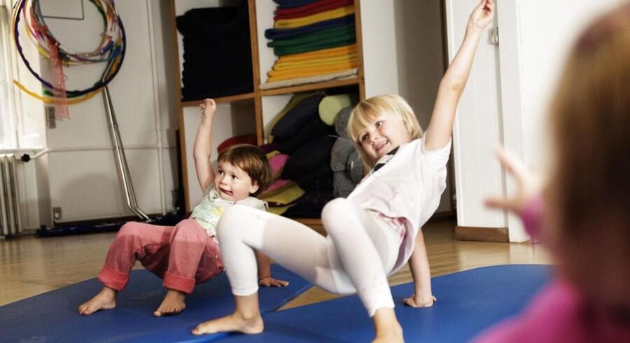 Børnene på yogaholdet leger de klassiske yogastillinger frem. Her er Anna (t.v) og Ursula en krabbe, der klapser med kloen. Foto: Erik Refner