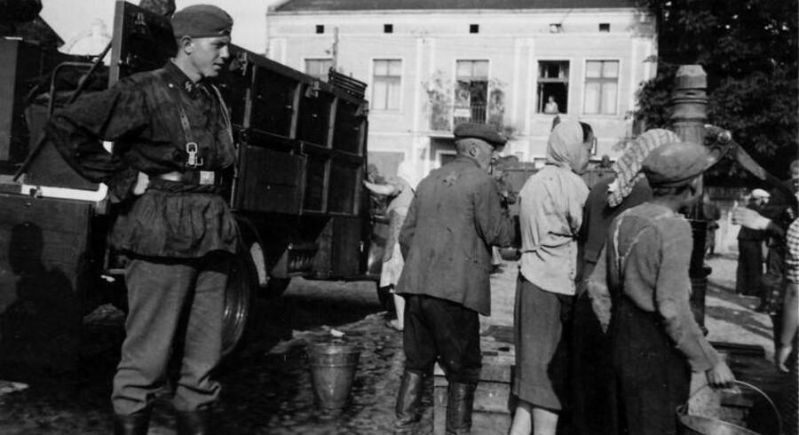 SS-mand tvinger jøder til at rengøre deres vogn, august 1941. Foto fra et mindealbum over en dansk SS-frivillig, der faldt i september 1941. Illustration fra bogen.