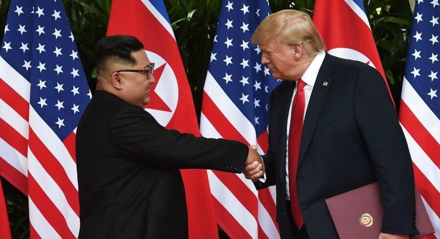 De trykkede hånd og trykkede hånd, da de endelig mødtes - USA´s præsident, Donald Trump, og Nordkoreas leder, Kim Jong-un. / AFP PHOTO / POOL / Anthony WALLACE