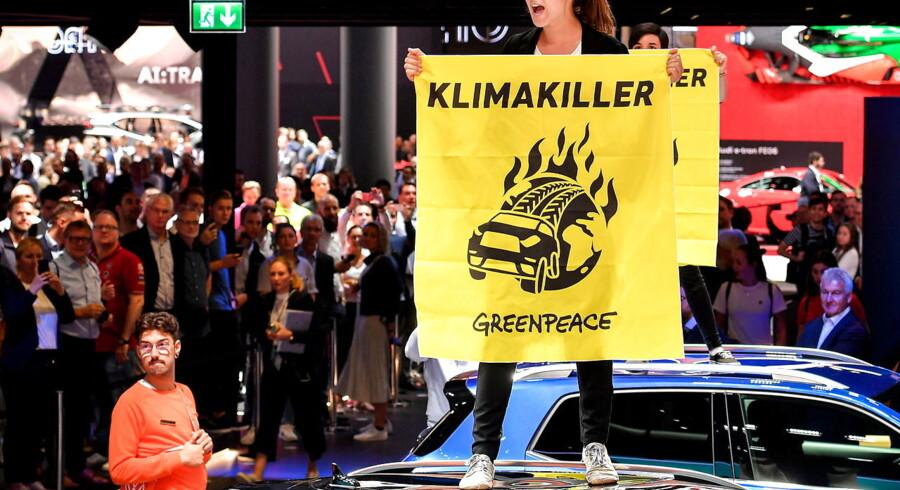 En Greenpeace-aktivist springer op på taget af en bil med et protestskilt under den årlige fejring af den tyske bilindustri på den internationale bilmesse i Frankfurt for et par uger siden.