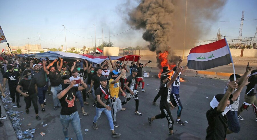 """Iraqi protesters take part in a demonstration against state corruption, failing public services, and unemployment, in the Iraqi capital Baghdad's central Khellani Square on October 4, 2019. - Iraqi security forces said """"unidentified snipers"""" killed four people across the capital Baghdad today, the fourth day of violent anti-government protests. (Photo by AHMAD AL-RUBAYE / AFP)"""
