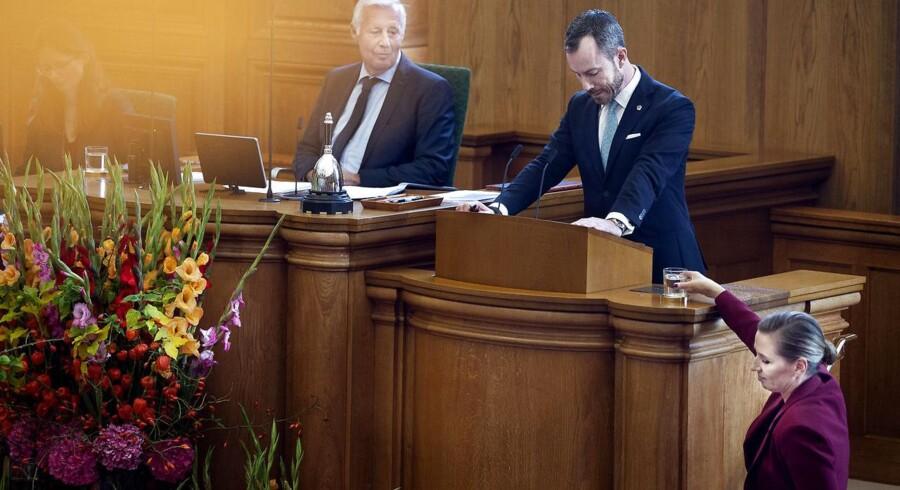 Statsminister Mette Frederiksen stiller et glas vand til Vestres formand Jakob Ellemann-Jensen, mens han er på talerstolen under åbningsdebatten i Folketinget på Christiansborg i torsdags.