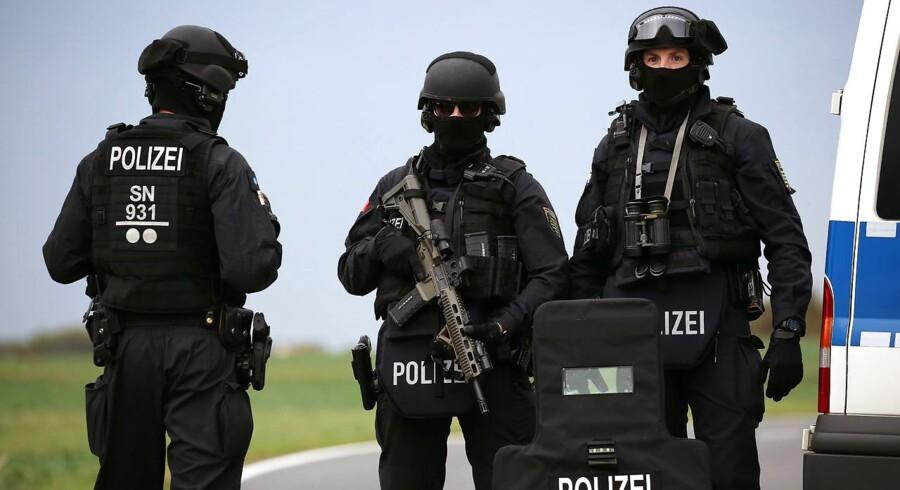 Kampklædte politifolk står vagt på vejen mellem Wiedersdorf og Landsberg ikke langt fra Halle, hvor flere personer i dag mistede livet.