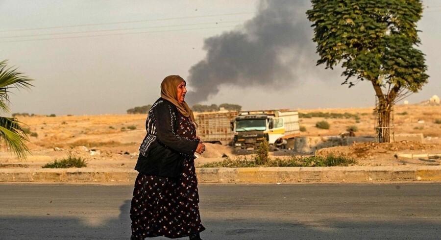 En syrisk kvinde ser til, mens røgen fra tyrkiske angreb stiger til vejrs.