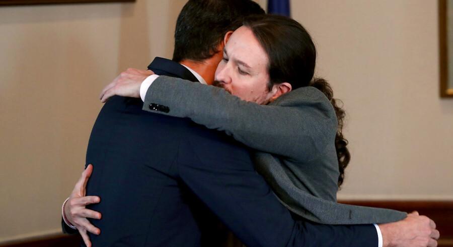 Podemos-lederen Pablo Iglesias lukker øjnene, mens han giver en sydeuropæisk mandfolkekrammer til en tydeligvis overrasket premierminister Pedro Sánchez.