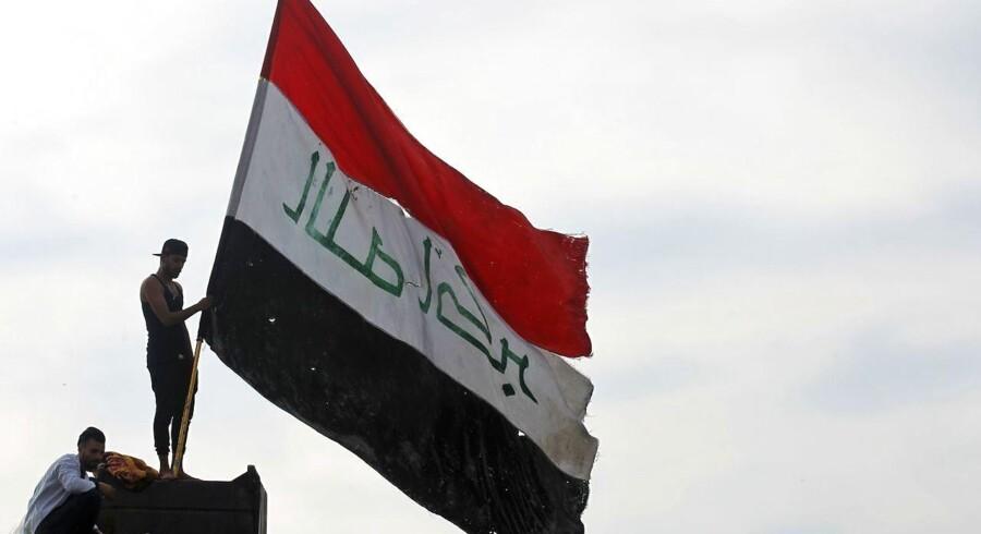 »Danmark fik sin grænse omtrent på samme tid, som Irak fik sin. Og efterhånden er Danmark og Irak flettet sammen. Der er danske soldater i Irak og irakiske indvandrere i Danmark,« skriver Hans Hauge. På billedet en irakisk demonstrant holder et irakisk flag. Foto: Ahmad Al-Rubaye / AFP