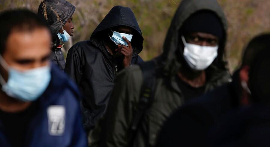 »Da den tyrkiske præsident Erdogan i sidste uge meddelte, at nu lukkede han døren til Europa op, var det i virkeligheden et nødråb,« skriver Uffe Ellemann-Jensen. På billedet bærer afrikanske migranter ansigtsmasker, som de har fået udleveret af græske grænsevagter 1. marts 2020. Foto: REUTERS/Elias Marcou