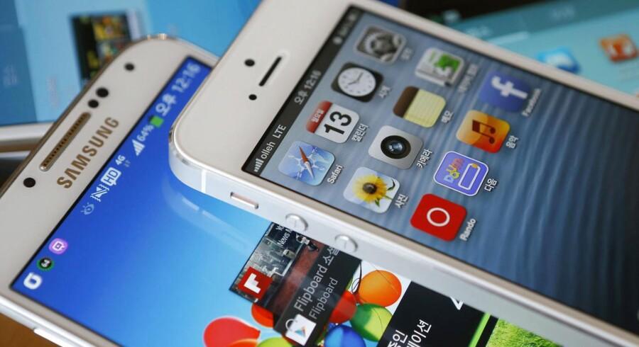Samsung og Apple er blevet enige om at droppe retssagerne mod hinanden i en lang række lande. I USA fortsætter slagsmålene om designligheder og ens funktioner dog. På billedet ses en iPhone 5 (øverst) og en Galaxy S4, som er væsentlige spillere i retsstridighederne. Arkivfoto: Kim Hong-Ji, Reuters/Scanpix