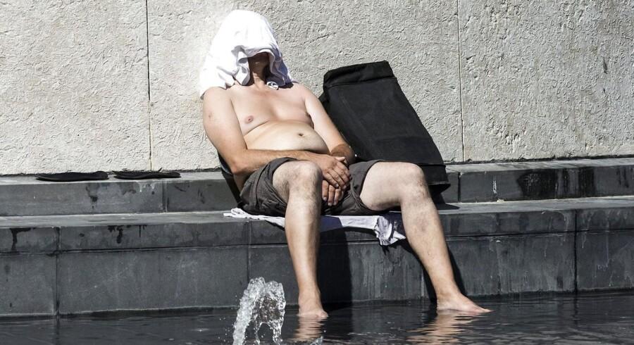 Denne turist i Paris har fattet i hvert fald lidt af budskabet - beskyt hovedet mod solen og køl kroppen ned med vand. Arkivfoto: Etienne Laurent.