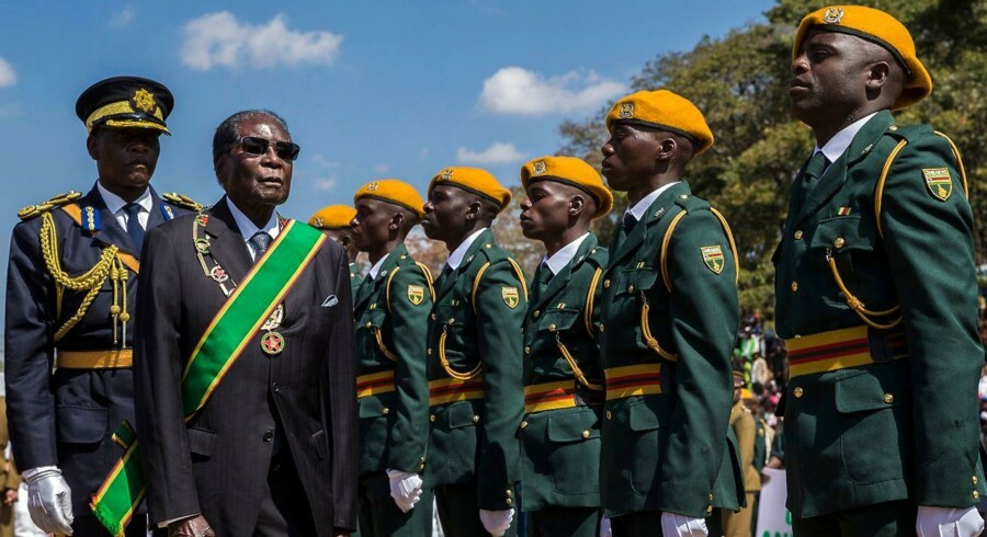 "(FILES) This file photo taken on August 14, 2017 shows Zimbabwe President Robert Mugabe (2L) inspecting a guard of honour during official Heroes Day commemorations held at National Heroes Acre in Zimbabwe. Zimbabwe's military appeared to be in control of the country on November 15, 2017 as generals denied staging a coup but used state television to vow to target ""criminals"" close to President Robert Mugabe. / AFP PHOTO / Jekesai NJIKIZANA"