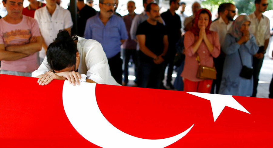 A relative of Gulsen Bahadir, a victim of Tuesday's attack on Ataturk airport, mourns at her flag-draped coffin during her funeral ceremony in Istanbul, Turkey, June 29, 2016. REUTERS/Osman Orsal