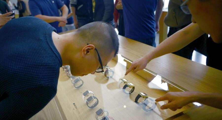 Fredag begyndte Apple-butikker verden over at præsentere det nye smartur, som kan forudbestilles men først købes fra 24. april. Her ser en kunde i Beijing på varen. Foto: Wang Zhao, AFP/Scanpix