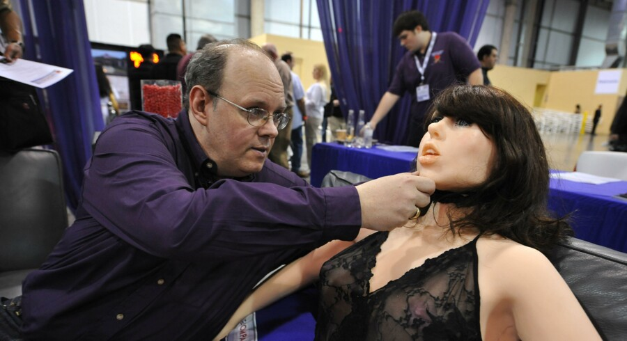 """Opfinderen af Roxxxy Douglas Hines præsenterede sexrobotten i 2010,adjusts the head of his company's """"True Companion"""" sex robot, Roxxxy, at the TrueCompanion.com booth at the AVN Adult Entertainment Expo in Las Vegas, Nevada, January 9, 2010. In what is billed as a world first, a life-size robotic girlfriend complete with artificial intelligence and flesh-like synthetic skin was introduced to adoring fans at the AVN Adult Entertainment Expo. AFP PHOTO / Robyn Beck"""