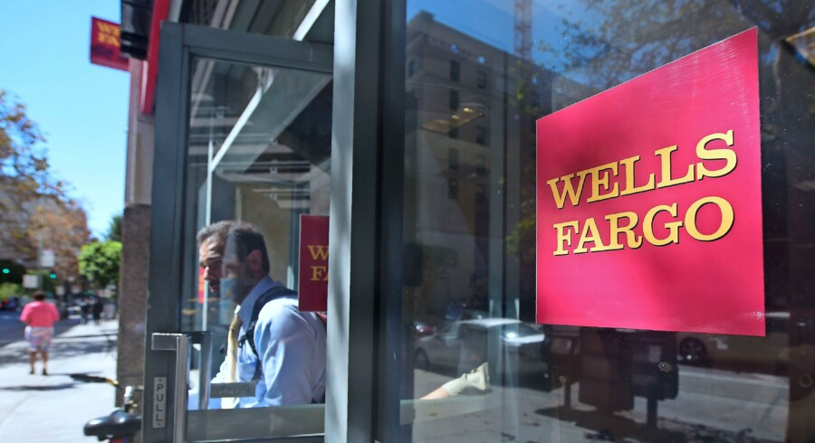 (FILES) This file photo taken on October 3, 2016 shows a man comes out of a branch of Wells Fargo bank in downtown Los Angeles in California. Large US banks reported lower third-quarter earnings on October 14, 2016 but beat analyst expectations, as Wells Fargo pledged anew to win back consumer trust after a bogus accounts scandal. Profits from JPMorgan Chase, Citigroup and Wells Fargo for the third quarter were lower compared with the year-ago period, revealing anew the drag on margins from ultra-low interest rates. / AFP PHOTO / FREDERIC J BROWN