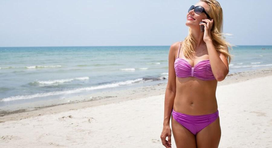 Det er stadig dyrt at gribe telefonen og ringe hjem fra stranden i Sydeuropa - og det bliver det ved med, selv om roamingpriserne skulle være blevet afskaffet til nytår. Foto: Iris/Scanpix