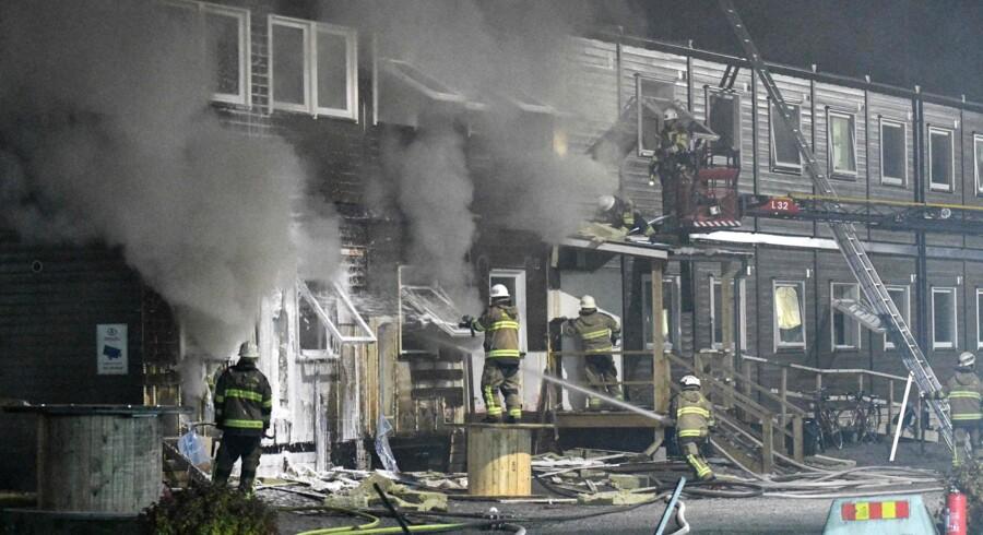 Brandmænd kæmper mod flammerne ved flygtningecentret i Fagersjö syd for Stockholm natten til søndag. Scanpix/Johan Nilsson