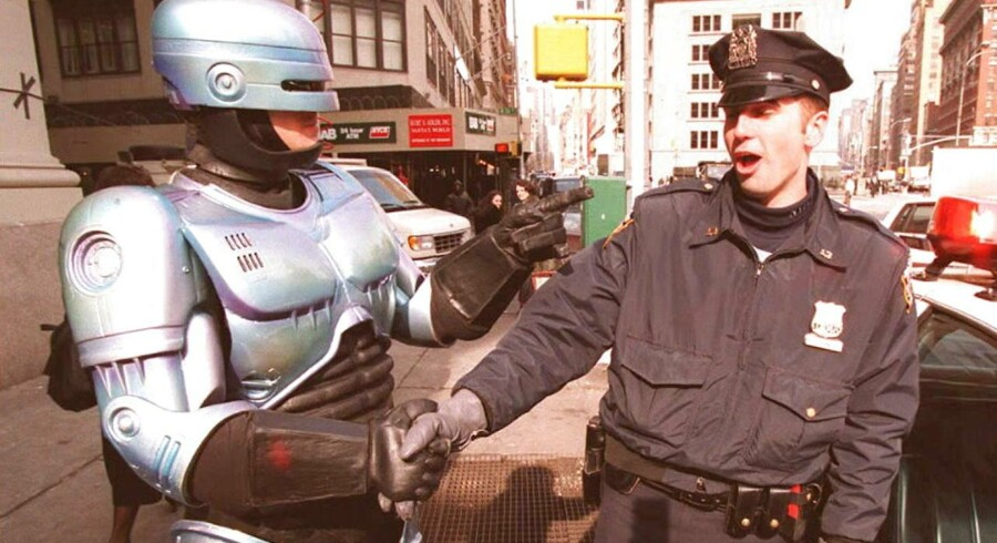 """En person klædt ud som filmkarakteren """"Robocop"""" hilser på en betjent i New York i 1996. Amerikansk og russisk militær ofrer store ressourcer på forskning i og udvikling af såkaldte dræberrobotter. På et møde i Geneve for nylig i FNs konvention for særlige våben (CCW) diskuterede man de etiske udfordringer i forbindelse med disse selvstændige våbenmaskiner, der kan udvælge og tilintetgøre mål uden menneskelig indblanding."""