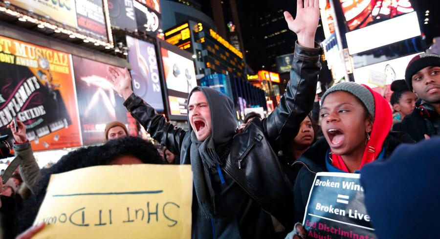 Demonstranter på Times Square protesterer over beslutningen om ikke at sigte politibetjenten, der dræbte Eric Garner.