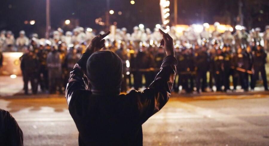 En demonstrant viser sin utilfredshed med politiet i Ferguson.