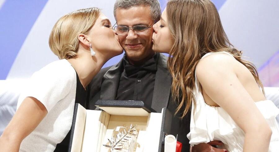Abdellatif Kechiche i midten med skuespillerne Adele Exarchopoulos og Lea Seydoux - og den gyldne palme. Den er nu røget på auktion.