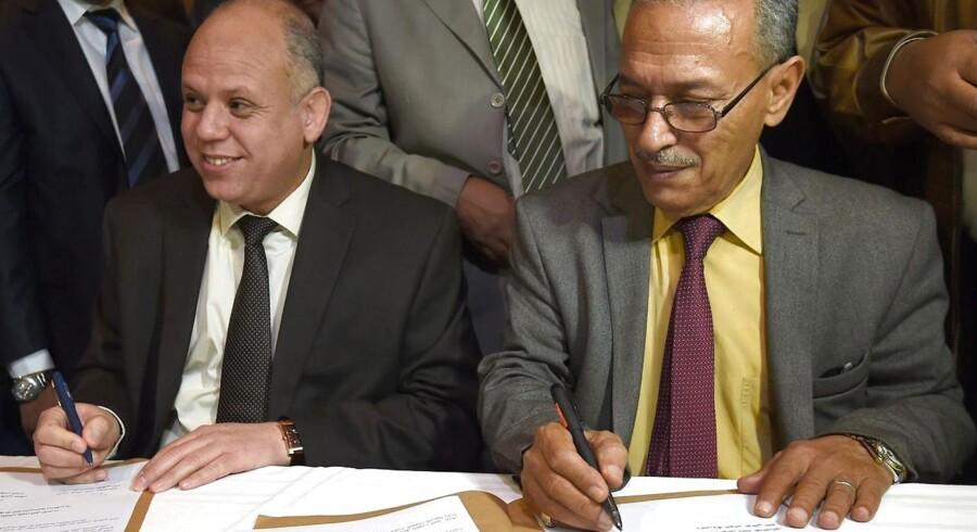 Awad Mohammed Abdul-Sadiq og Ibrahim Fethi Amish repræsenterede hver sin libyske regering, da aftalen, der skal bane vejen for en samlet regering i landet, blev underskrevet i Tunesien