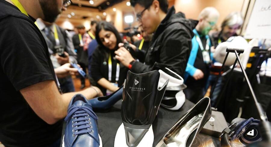 Deltagere kigger på smart-skoen Digisole. Gennem en app på sin smartphone kan brugeren både stramme skoen, varme fødderne og måle brændte kalorier. AFP PHOTO / DAVID MCNEW