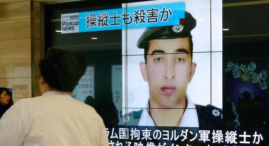 Fodgængere går forbi en stor skærm i Tokyo, der viser nyheden om Islamisk Stats henrettelse af den jordanske pilot Maaz al-Kassasbeh.