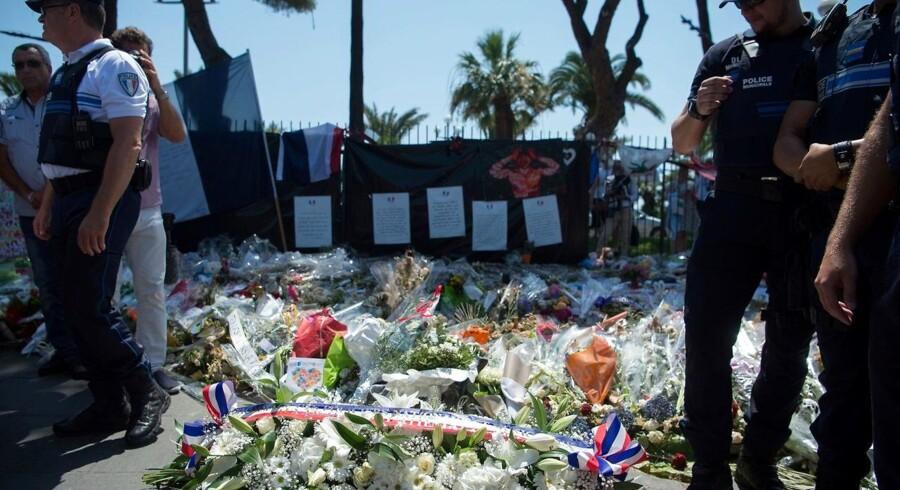 Politimænd står vagt ved blomsterne, der blev efterladt til ære for de døde i angrebet i Nice d. 14. juli 2016. Et fransk magasin er kommet i modvind, efter at have meget grafiske billeder af angrebet og dets ofre på forsiden.