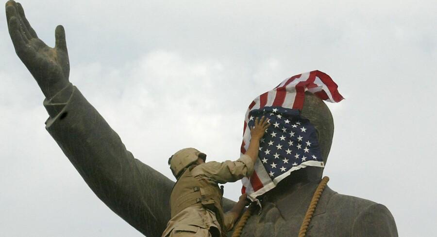En amerikansk soldat dækker en statue af Saddam Hussein med Stars & Stripes i Bagdad 2003. ?Foto: Ramzi Haidar