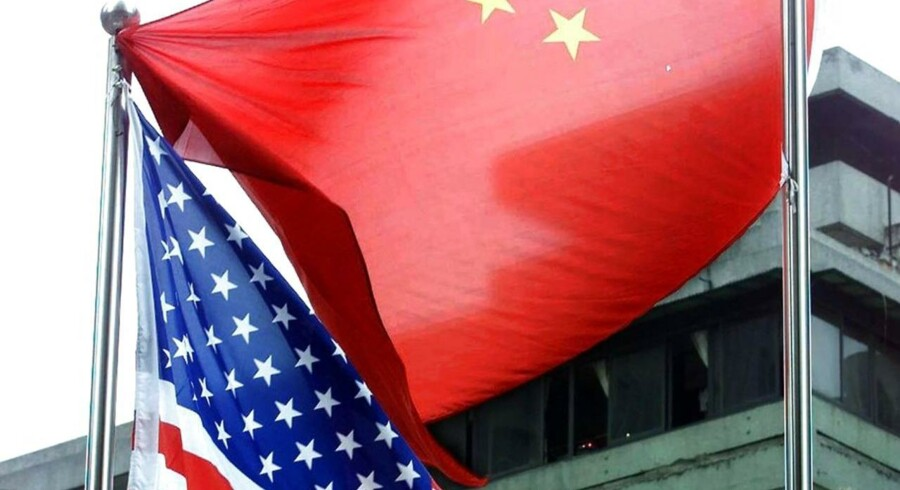 A Chinese national flag gets stuck on a flagpole flying an American flag in Beijing 04 July 2000. Proud of its famous Stars and Stripes, the United States spent some 1.1 million USD last year to import American flags from abroad, and nearly half of those were made in China. (ELECTRONIC IMAGE) AFP PHOTO/GOH Chai Hin