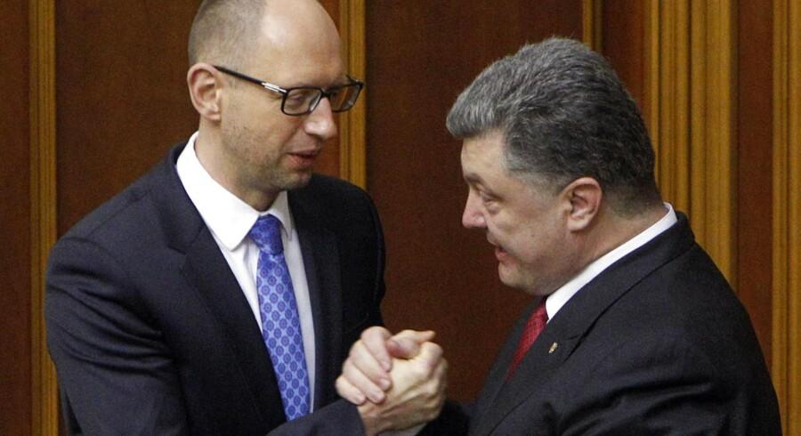 Ukraines præsident Petro Poroshenko (til højre) giver håndtryk med premierminister Arseny Yatseniuk efter ratifikationen af tirsdagens aftale.