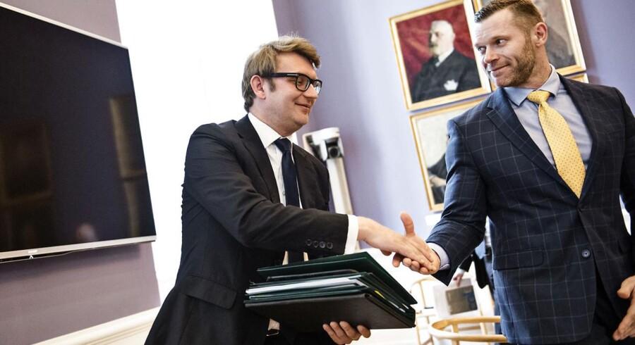 Erhvervs- og vækstminister Troels Lund Poulsen (t.h.) giver hånden til Liberal Alliances Joachim B. Olsen (t.v.). Arkivfoto.