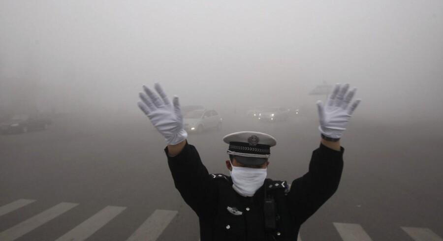 En politimand dirigerer trafikken gennem den tunge smog i Harbin i Heilongjiang-provinsen. Danske firmaer som Topsøe og rådgivere kan levere udstyr og løsninger for milliarder.
