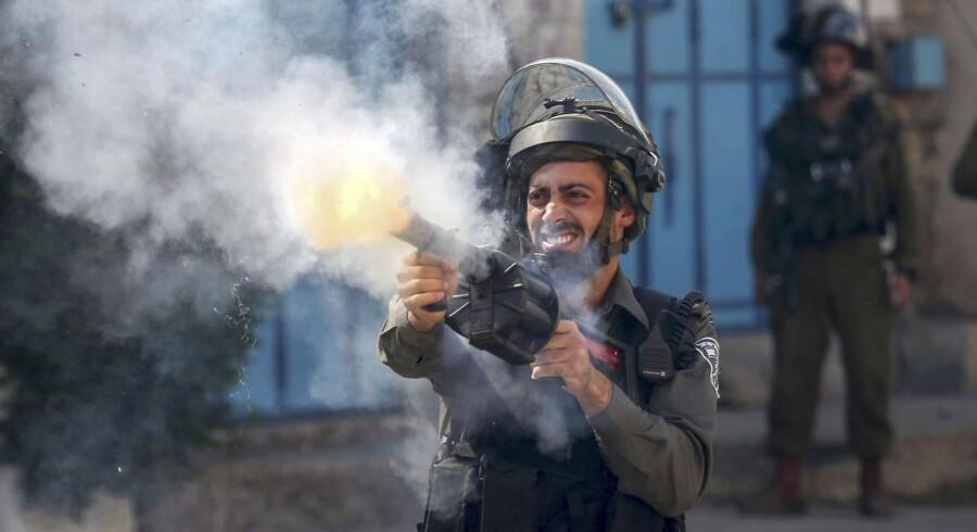En israelsk soldat skyder tåregas mod palæstinensiske demonstranter under fredagens sammenstød på Vestbredden.