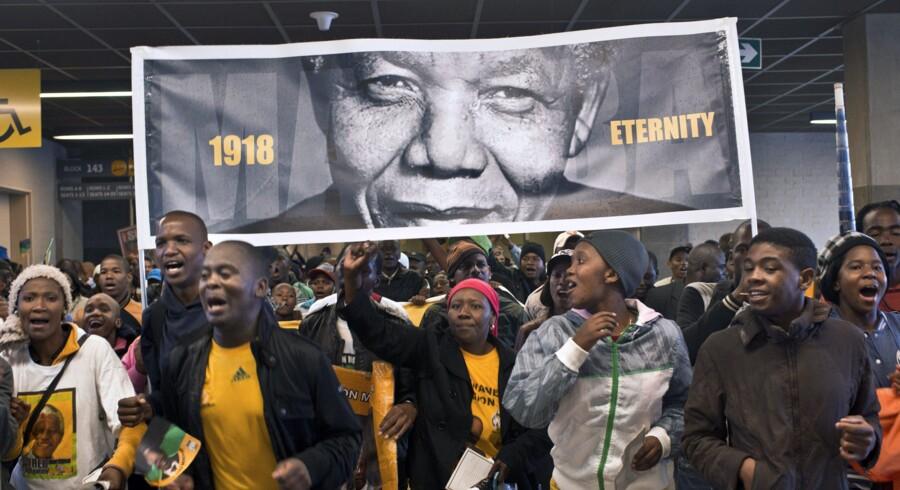 Fra 1918 til evigheden præsenteres Nelson Mandela på denne plakat, som sydafrikanere i går havde med til mindehøjtideligheden. Foto: Pedro Ugarte