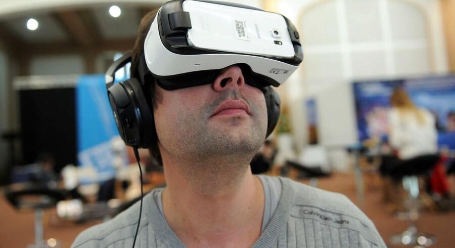 Ved at skubbe sin mobiltelefon ind i et sæt briller træder man ind i den virtuelle virkelighed (»virtual reality«), hvor ens bevægelser registreres af telefonens sensorer, så billedet bevæger sig i den retning, som man vender sig eller kikker. Her er det Samsungs Gear VR-briller, som afprøves. Arkivfoto: Iroz Gaizka, AFP/Scanpix