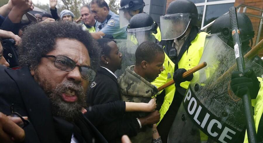 ARKIVFOTO. Demonstranter foran politiets hovedkontor i Ferguson i oktober. Da politiet skød og dræbte den 18-årige Michael Brown udløste det omfattende demonstrationer i hele landet.