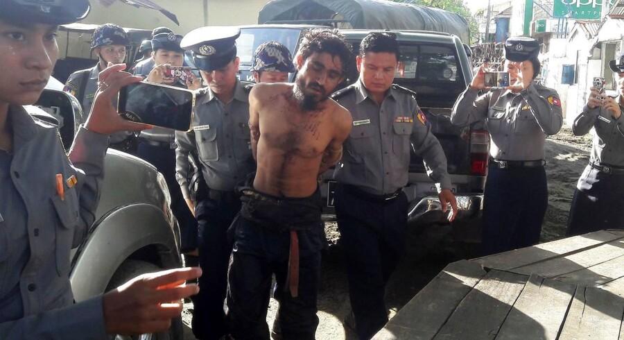 Manden på billedet mistænkes for at stå bag oprør ved grænsen og er her ved at blive taget med til en politistation i Rakhine i Myanmar. Billedet er taget 9. oktober 2016. AFP PHOTO / STRINGER