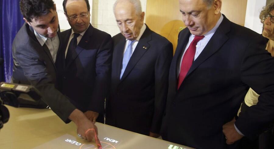 Den franske præsident François Hollande (nummer to fra venstre) og Israels president Shimon Peres (nummer to fra højre) lytter, mens det israelske softwarefirma Primesenses direktør for forretningsudvikling, Jeremie Kletzkine (til venstre) forklarer om 3D-sensorteknologien. Det skete under et besøg i Tel Aviv i sidste uge. Nu har Apple købt selskabet. Arkivfoto: Philippe Wojazer, Reuters/Scanpix