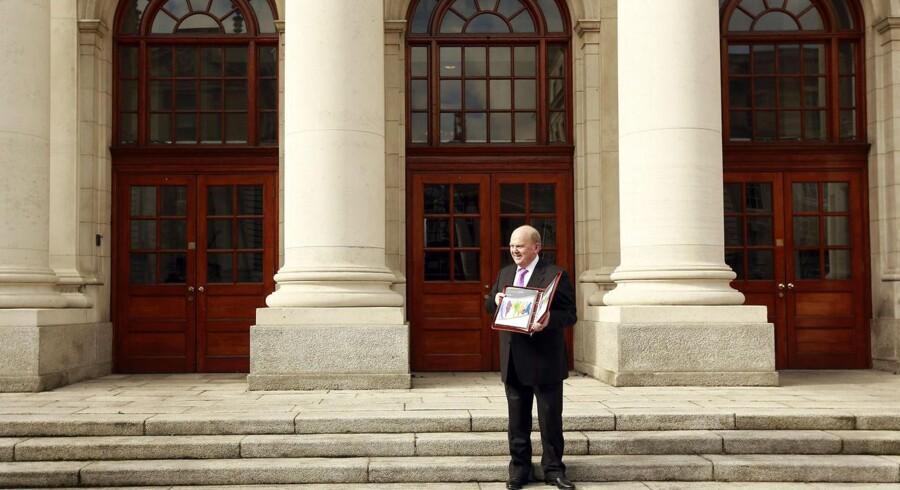 Den irske finansminister, Michael Noonan, er her på vej ind i det irske parlament, Dáil, med det nye 2015-budget, som blandt andet afskaffer et omdiskuteret skattehul, som internationale selskaber har nydt godt af til at nedbringe deres selskabsskat betragteligt. Foto: Cathal McNaughton, Reuters/Scanpix