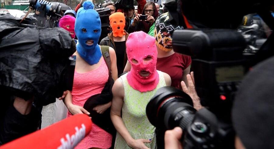 Iført masker forlader medlemmer af Pussy Riot her politistationen i Adler nær Sotji efter at have været blevet anholdt - beskyldt for tyveri fra et hotel.