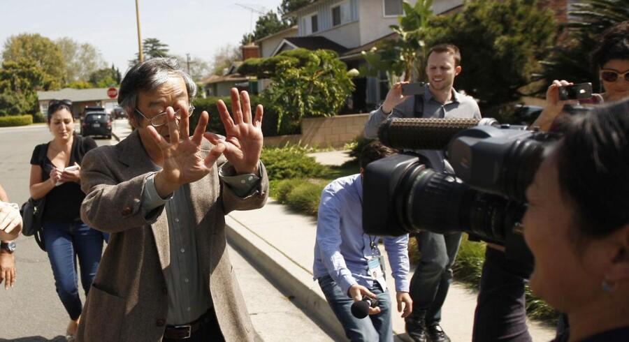 Satoshi Nakamoto, der menes at stå bag den populære Bitcoin-valuta, omringes af reportere, da han forlader sit hjem.