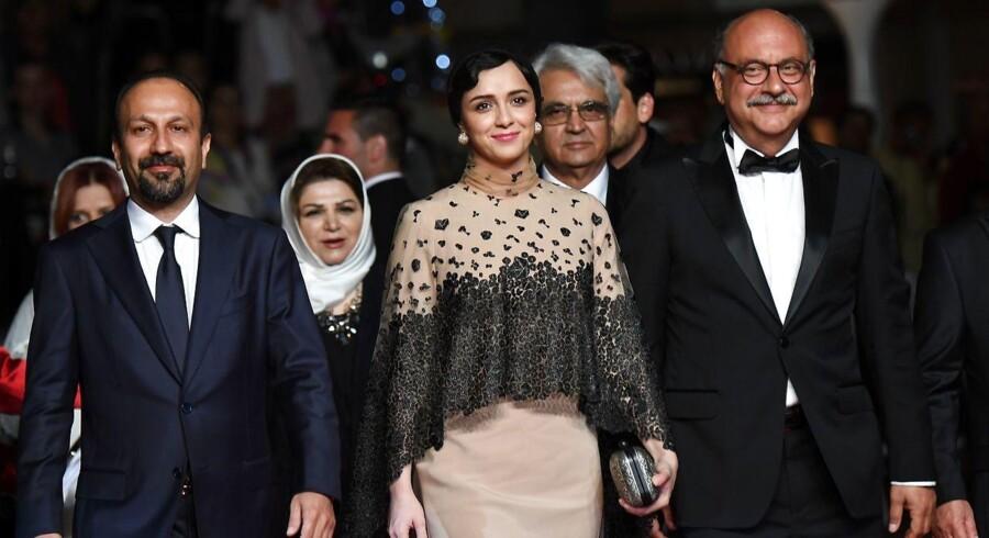 """Instruktøren Asghar Farhadi (til venstre), skuespillerne Taraneh Alidoosti og Babak Karimi poserer da de ankommer ved sidste sommers visning i filmfestivalen i Cannes af """"The Salesman (Forushande)"""", der nu er blevet oscarnomineret. Alidoosti har nu truet med at boycotte oscaruddelingen."""