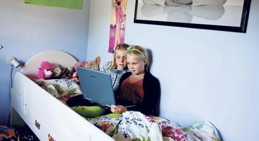 Anna og Maja Elmgreen hygger sig på børneværelset med internettet. Foto