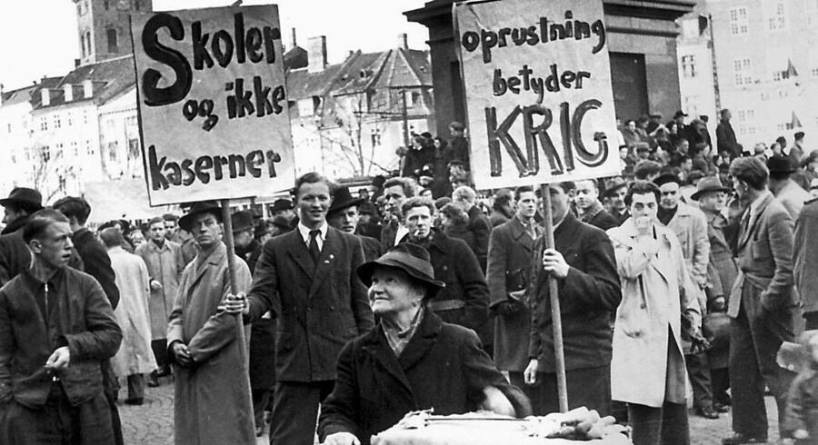 Protesterne mod Den Kolde Krig, mod militær oprustning og mod Atlantpagten tog til i 1949. Lirekassedamen har placeret sig centralt på slotspladsen foran Christiansborg. Hun er hverken for eller imod, men de mange mennesker skulle nok kunne ryste en skilling af. Foto: Walther Månsson