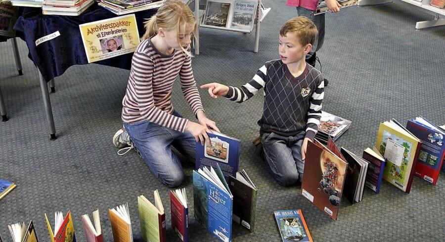 Er den teknologiske udvikling godt i gang med at gøre bibliotekerne overflødige - eller er der tværtimod mere brug for bibliotekerne til at give både børn og voksne lyst til at læse? Meningerne er delte. Her stiller børn på Ringkøbing Bibliotek bøger op til »bog-domino«.
