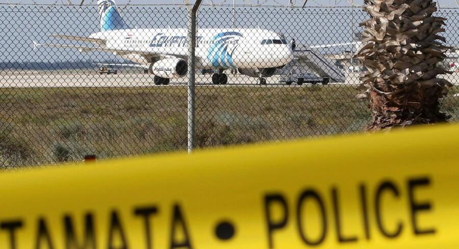 Kort forinden flykapreren blev anholdt, blev et af hans gidsler set kravle ud af det parkerede flys cockpit-vindue.