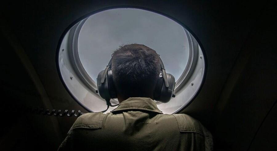 En indonesisk militærmand stirrer intenst ud af vinduet i et transportfly i håb om at opdage rester af AirAsia-flyet, der søndag styrtede i havet med 162 mennesker ombord.