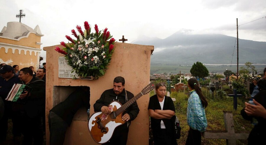 De lokale i landsbyen Alotenango deltager i en begravelse. I baggrunden vulkanen Fuego.